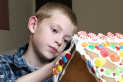 Ginger kid. Young boy building a christmas gingerbread house Royalty Free Stock Images