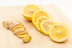 Ginger and lemon slices on wooden cutting board. Sliced ginger and lemon slices on wooden cutting board Stock Image