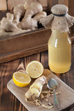 Ginger and lemon syrup. Peeled ginger root with lemons and a bottle of ginger syrup in background. Shallow dof royalty free stock photography