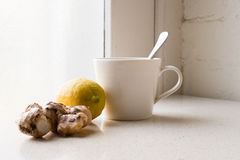 Ginger, lemon and white cup next to window Stock Image