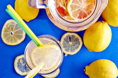 Ginger lemonade in glass with pithcer on back. Royalty Free Stock Image