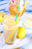 Ginger lemonade in glass with pithcer on back. Royalty Free Stock Photos