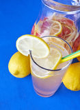 Ginger lemonade in glass with pithcer on back. Stock Photo