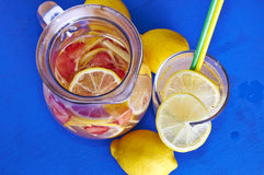 Ginger lemonade in glass with pithcer on back. Stock Photography
