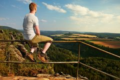 Ginger man sit on handrail at peak of rock and watch to landscape.  Sunny day in rocky mountains. Hiker with grey shirt, pants and Royalty Free Stock Image