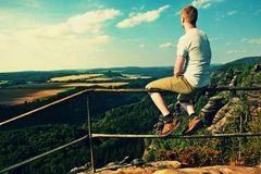 Ginger man sit on handrail at peak of rock and watch to landscape.  Sunny day in rocky mountains. Hiker with grey shirt, pants and Royalty Free Stock Images