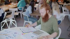 Ginger man working in cafe and drink coffee on table graph and papper. Behind him cheerful group of young peoples stock video