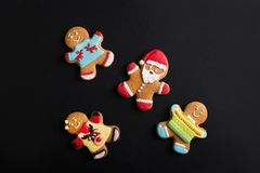Ginger men with colored glaze on a black background . Gingerbread Stock Photos