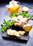 Ginger, mint and tea. Fresh ginger,herb and tea on a table royalty free stock image