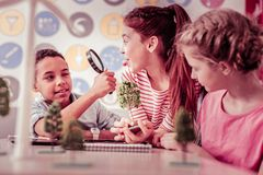 Ginger mischievous girl showing tongue to her classmate. Carrying magnifying glass. Ginger mischievous girl showing tongue to her classmate while he playing with royalty free stock photos