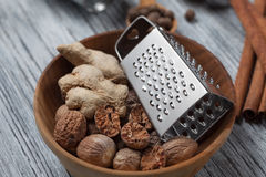 Ginger with nutmeg and grater in bowl on wood Stock Photo