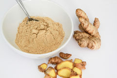 Ginger powder in bowl with metal spoon, ginger root and ginger pieces outside bowl, isolated on white Stock Photo