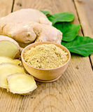 Ginger powder in a bowl with the root and leaves Royalty Free Stock Image