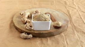Ginger Powder i en bunke och en rå och torkad ingefära på en trätabell royaltyfria foton