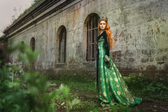 Ginger queen near the castle. Red-haired woman in a green medieval dress near the castle Royalty Free Stock Images