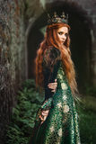 Ginger queen near the castle. Red-haired woman in a green medieval dress near the castle Stock Images