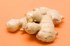 Ginger root. On orange background Stock Photos