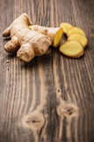 Ginger root. Sliced ginger root on rustic wooden background Stock Photos