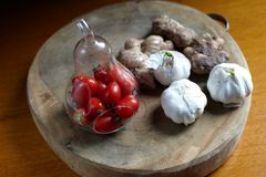 Ginger root and Cherry tomato in pear-shaoe bottle Royalty Free Stock Photos