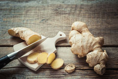 Ginger root on cutting board on rustic wooden kitchen table. Royalty Free Stock Images