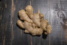 Ginger root lies on black wooden table Stock Photos