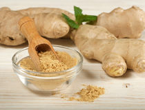 Ginger root and powder. On wooden background Royalty Free Stock Photography