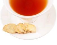 Ginger Root Slices och en kopp tedropp Royaltyfri Bild