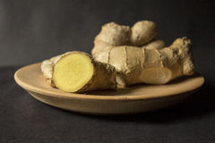 Ginger. Roots on a wooden plate Royalty Free Stock Image