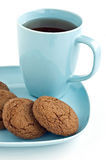 Ginger snaps and tea. Freshly baked ginger snaps with tea on robin's egg blue plate and mug,isolated on white background in vertical format Stock Images