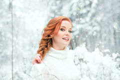 Ginger sweet girl in white sweater in winter forest. Snow december in park. Portrait. Christmas cute time. Ginger sweet girl in white sweater in winter forest stock image