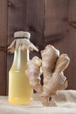 Ginger and syrup. Ginger root and bottle with ginger syrup. Shallow dof royalty free stock image