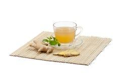 Ginger tea. Herbal Ginger tea and fresh ginger on bamboo matt Royalty Free Stock Photos