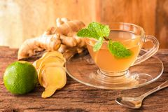 Ginger tea - Cup of ginger tea with green lemon. Ginger slices and mint leaf on a rustic wooden background, Beverage concept, Close up, Selective Focus royalty free stock photos