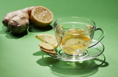 Ginger tea in a cup of glass on a green background. Royalty Free Stock Photos