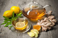 Ginger tea. Cup of ginger tea with honey and lemon on wooden table