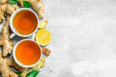 Ginger tea in cup and lemon. On rustic background stock images