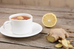 Ginger tea in a cup on wooden background. Aroma, drink, fresh, glass, health, healthy, homeopathy, hot, ingredient, medicine, natural, organic, raw, seasoning stock image