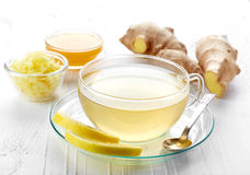 Ginger tea. And fresh ginger root on white wooden background royalty free stock image