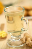 Ginger Tea. Freshly prepared hot ginger tea made of fresh ginger root served in glass (Selective Focus, Focus on the front of the rim and the handle of the glass Royalty Free Stock Photography