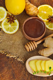 Ginger tea ingredients. Honey, lemon and ginger. Wooden background with sackcloth. Close-up. Top view. Selective focus Royalty Free Stock Photos