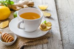 Ginger tea and ingredients on rustic wood background. Copy space Stock Image