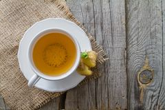 Ginger tea and ingredients on rustic wood background. Copy space Stock Photo