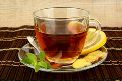 Ginger tea-ingwertee on brown mat with lemon Royalty Free Stock Images