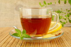 Ginger tea-ingwertee on wooden mat with lemon Stock Photos