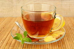 Ginger tea-ingwertee on wooden mat with lemon Stock Photography