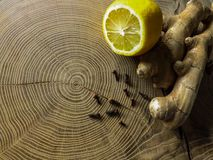 Ginger tea with lemon and cloves on wooden table stock photography