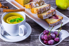 Ginger tea with lemon, mint and cherry cake, closeup.  Royalty Free Stock Photo
