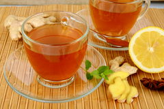 Ginger teas on wooden mat with lemon Stock Photos
