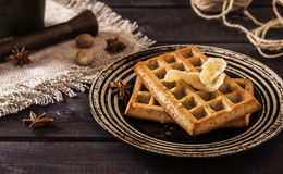 Ginger waffles with honey. Ginger waffles topped with honey and decorated with candied ginger with anise and nutmeg on a dark wooden background Stock Images