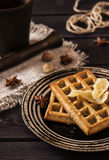 Ginger waffles with honey. Ginger waffles topped with honey and decorated with candied ginger with anise and nutmeg on a dark wooden background Royalty Free Stock Photos